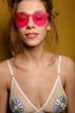 La fille avec les cheveux rassemblés et le dessus du maillot de bain dans les verres roses est sur un fond jaune avec les yeux fe Images stock