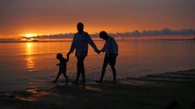 La fille avec les enfants font des promenades et jouent sur la plage au temps de coucher du soleil banque de vidéos