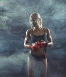 La fille avec les gants se reposant après la formation Photographie stock libre de droits