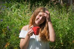 La fille avec les prises rouges de cheveux dans sa main une tasse rouge avec le thé sur le fond de l'herbe de pré photos stock