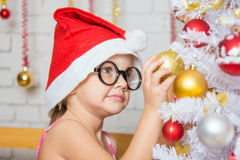 La fille avec les verres ronds accroche des boules sur un arbre de Noël neigeux de nouvelles années Image stock