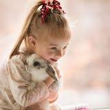 La fille avec la trisomie 21 étreint le lapin Photographie stock