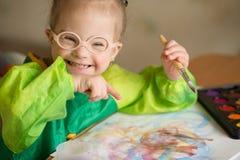 La fille avec la trisomie 21 dessine des peintures photos libres de droits