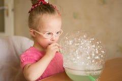 La fille avec la trisomie 21 fait l'exercice de respiration d'orthophonie Images libres de droits