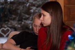 La fille avec la tristesse dans ses yeux s'assied sur le recouvrement du type et regarde la fenêtre photos libres de droits