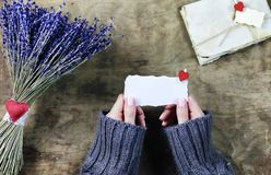 La fille avec un bouquet de lavande fleurit sur la table en bois Image libre de droits