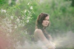 La fille avec un bouquet des fleurs sauvages par temps nuageux 2 Image stock