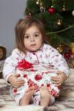 La fille avec un cadeau sous l'arbre de Noël Photo libre de droits