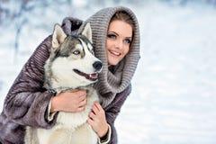 La fille avec un chien enroué à l'arrière-plan de forêt d'hiver, se ferment  Photographie stock libre de droits
