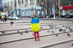 La fille avec un drapeau se tient sur la place Image libre de droits