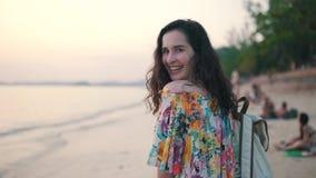 La fille avec un sac à dos marche sur la plage banque de vidéos