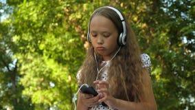La fille avec un téléphone dans des écouteurs écoute la musique et chante en parc d'été banque de vidéos