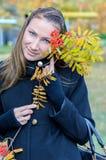 La fille avec une branche de cendre de montagne. Photo stock