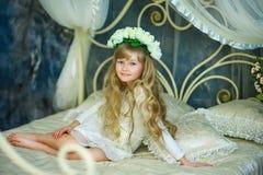 La fille avec une guirlande des roses blanches Photo stock