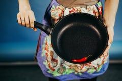 La fille avec une poêle Sont le poivre pointu rouge du Chili sur une poêle photos stock