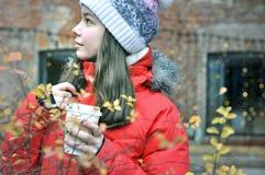 La fille avec une tasse de café pendant l'hiver regarde loin Photo libre de droits