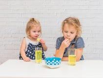 La fille, bébé mangeant des pommes chips et buvant la soude, pas santé photos libres de droits
