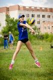 La fille bat la boule dans le volleyball malaxant avant de jouer l'amateu photographie stock