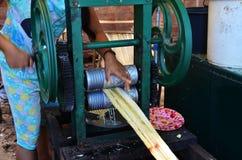 La fille birmanne a fait le jus de canne de sucre par la machine manuelle de fabricant à vendre le voyageur image stock