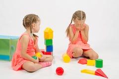 La fille a blessé une autre fille jouant avec des jouets Image stock