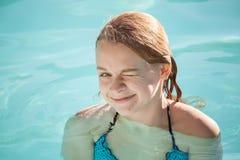 La fille blonde adolescente heureuse cligne de l'oeil dans la piscine extérieure Image stock
