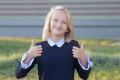 La fille blonde adorable avec le livre dans des mains s'approchent de l'école L'écolière aime apprendre et lire photo libre de droits