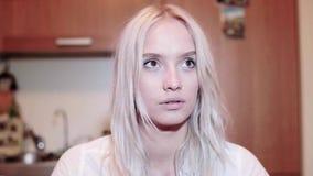La fille blonde assez de sourire avec le visage curieux regarde fixement avec les yeux bruns mignons clips vidéos