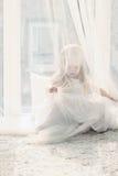 La fille blonde assez petite s'assied près de la grande fenêtre et se cache Image libre de droits