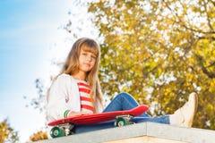 La fille blonde avec de longs cheveux s'assied près de la planche à roulettes Image stock