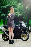 La fille blonde avec des sports font du vélo dans une robe, photo tendre d'été Photo libre de droits