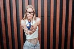 La fille blonde avec des verres regarde sur l'appareil-photo et tient le pistolet d'eau dans des mains Elle est très sérieuse d'i image libre de droits