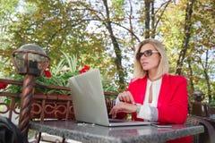 La fille blonde avec des verres s'assied à l'ordinateur portable Photo libre de droits