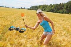 La fille blonde avec une tapette de mouche conduit loin le bourdon Photos stock