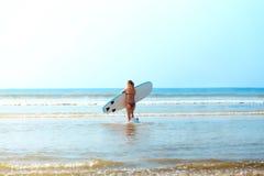 La fille blonde blanche de surfer avec la planche de surf va à la mer photo stock