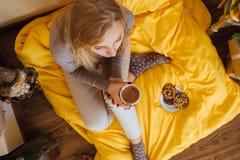 La fille blonde buvant de son café, mangent des biscuits et ont lu un livre Photo stock