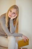 La fille blonde buvant de son café, mangent des biscuits et ont lu un livre Images stock
