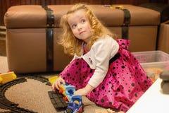 La fille blonde caucasienne mignonne de cheveux bouclés joue avec des jouets de train d'intérieur Image libre de droits