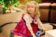 La fille blonde caucasienne mignonne de cheveux bouclés joue avec des jouets de train d'intérieur sur le fond de tache floue de l Photos libres de droits