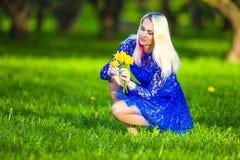 La fille blonde caucasienne reprenant fleurit pour le groupe de jonquilles Image stock