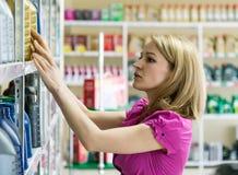 La fille blonde choisit l'huile de moteur dans le magasin de pièces d'auto Photos libres de droits