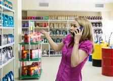 La fille blonde choisit l'huile de moteur dans le magasin de pièces d'auto, consulte par le téléphone Image libre de droits
