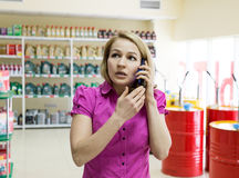 La fille blonde choisit l'huile de moteur dans le magasin de pièces d'auto, consulte par le téléphone Photos stock