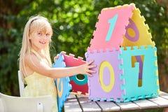 La fille blonde construit une maison miniature image stock