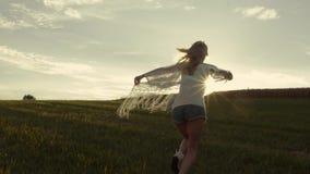 La fille blonde court dans le mouvement lent, belle nature, soleil lumineux banque de vidéos
