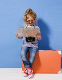 La fille blonde d'enfant avec la valise rose de vintage et la ville tracent prêt Image libre de droits