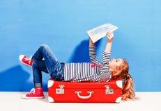La fille blonde d'enfant avec la valise rose de vintage et la ville tracent prêt Photos stock