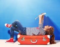 La fille blonde d'enfant avec la valise rose de vintage et la ville tracent prêt pour des vacances d'été Concept de voyage et d'a Image stock