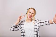 La fille blonde dans des écouteurs avec la langue collant apprécie la musique et dupe autour de la danse sur le fond blanc image libre de droits