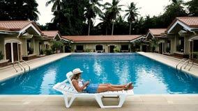 La fille blonde dans le chapeau, combinaisons se trouve par la piscine et regarde pour téléphoner banque de vidéos