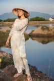 la fille blonde dans le Vietnamien habillent des sourires contre des lacs de pays Image stock